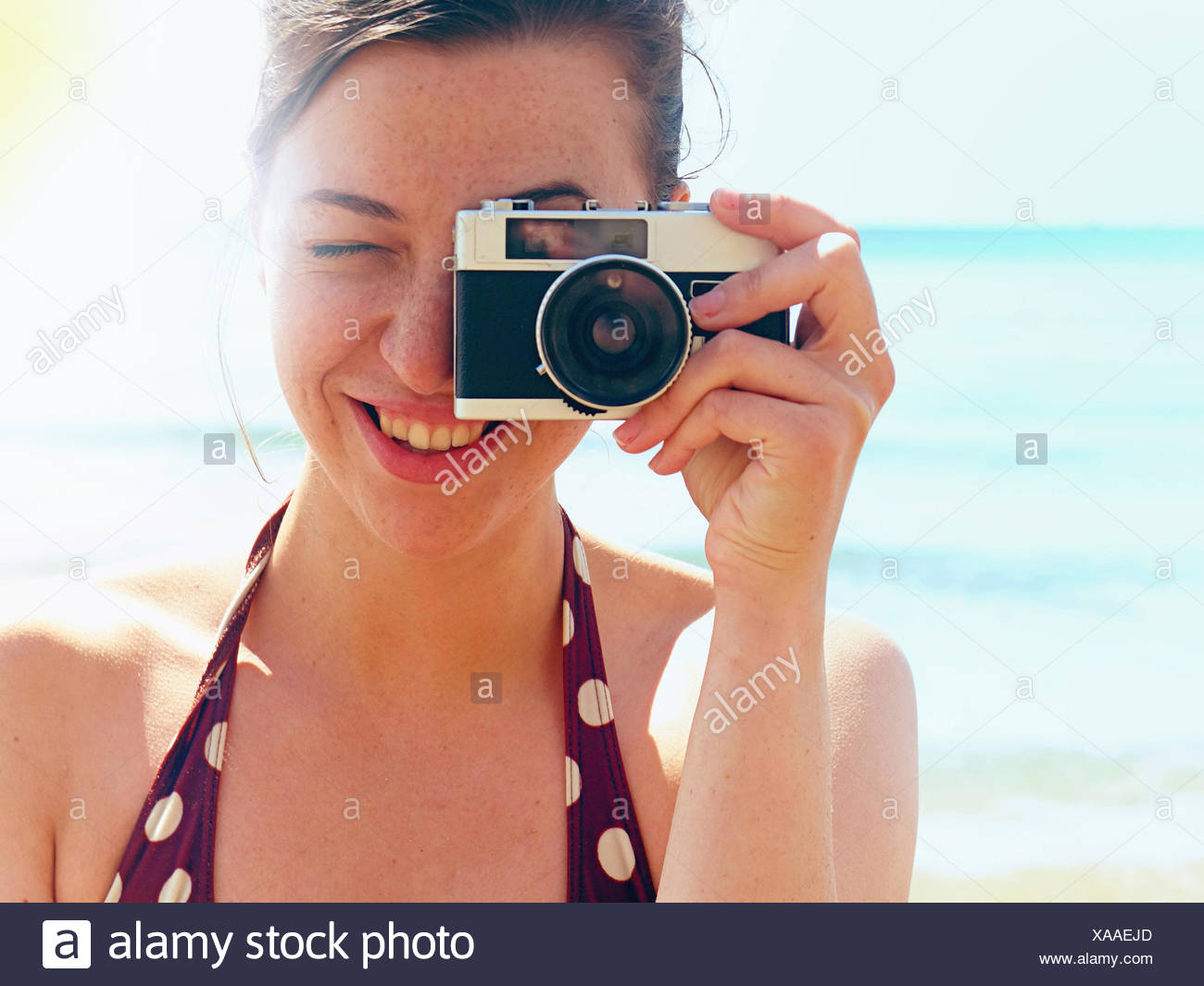 Young woman using camera on beach - Stock Image