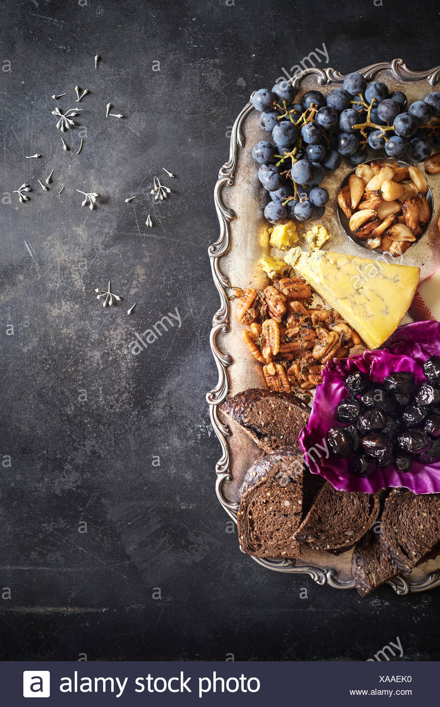 Charcuterie tray with grapes, cheeses, nuts, roasted garlic, olives and toast on a festive metal tray on a dark rustic surface. - Stock Image