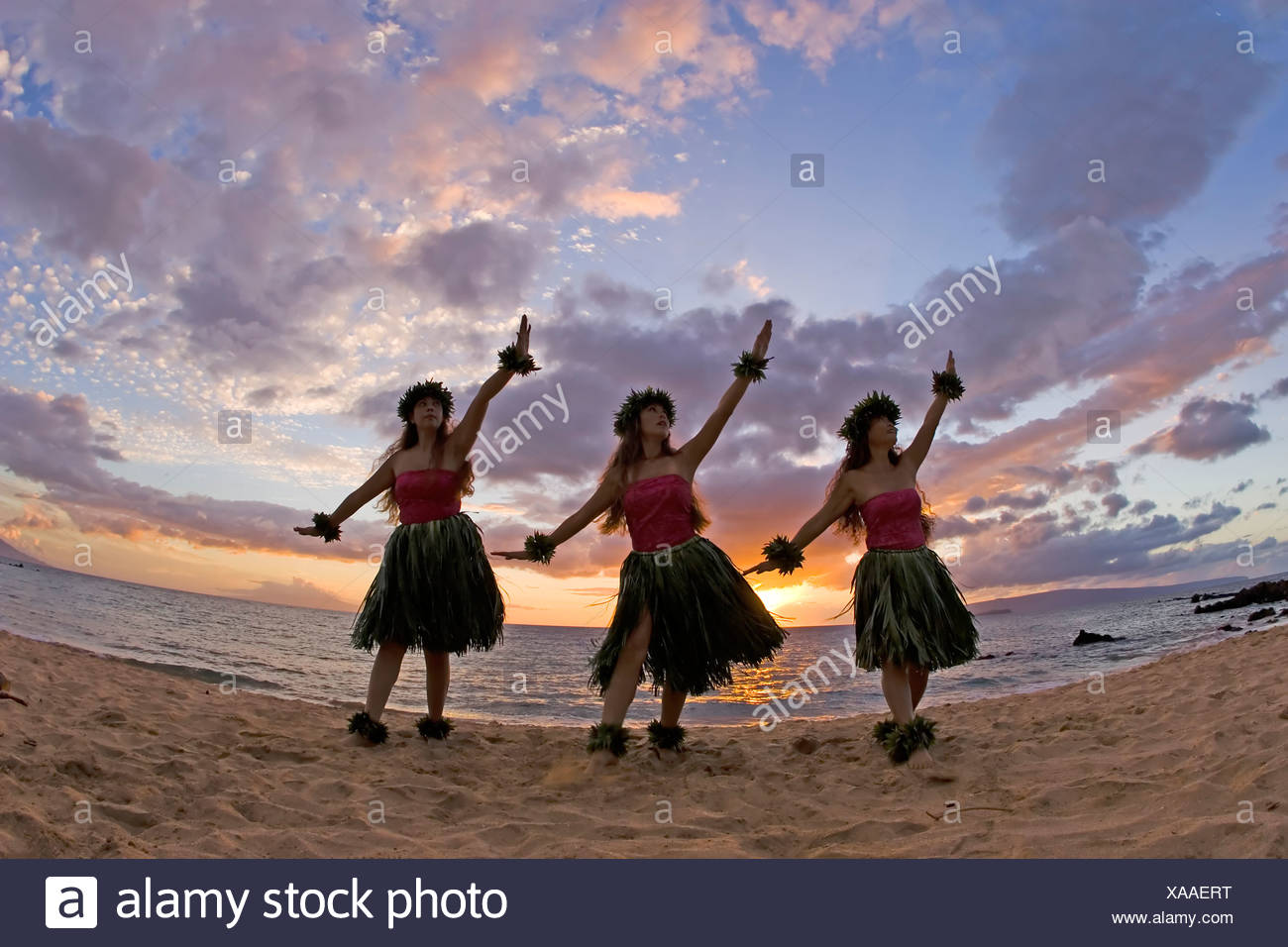 Three hula dancers in ti leaf skirts dance on the beach at sunset at Makena, Maui. Stock Photo