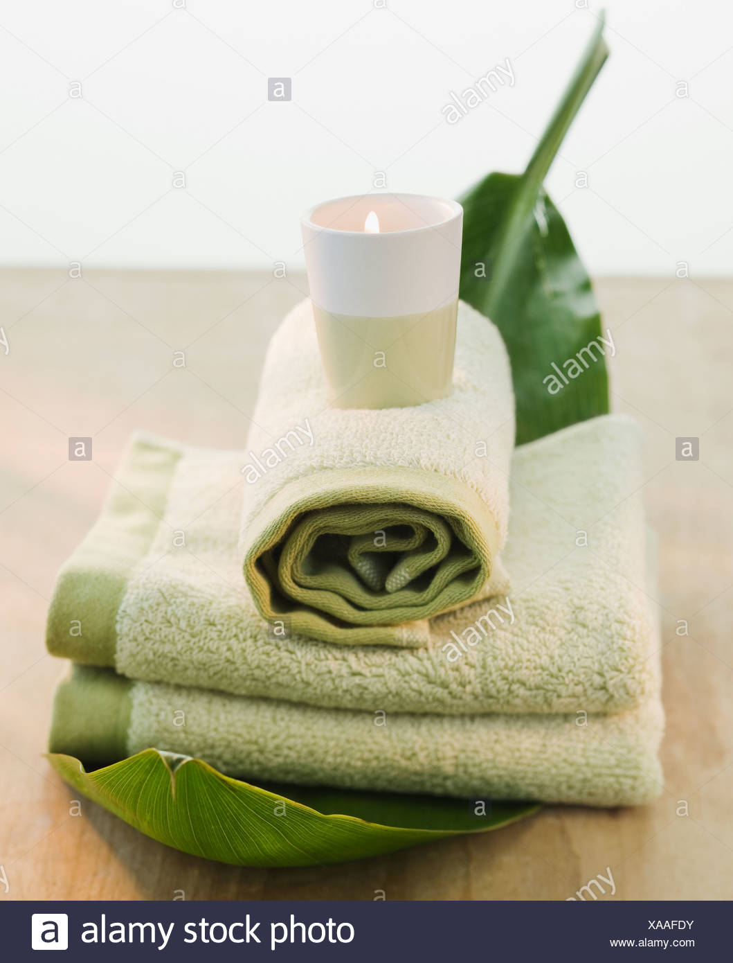 Candle on rolled towels - Stock Image