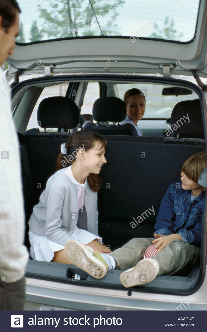 Siblings sitting in back of station wagon, parents watching - Stock Image