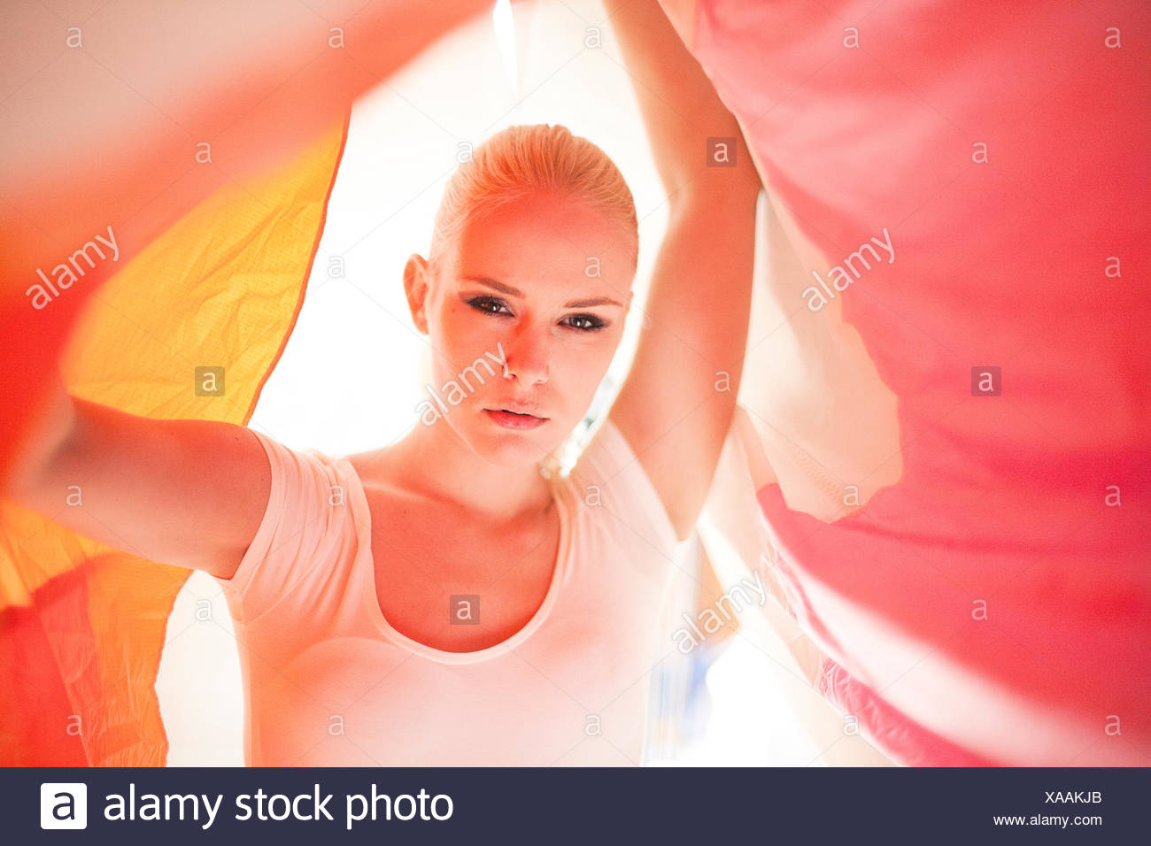 young woman between coloured sailings - Stock Image