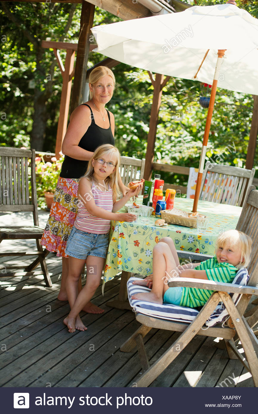 Mother and daughters (6-7) eating hot dogs in garden Stock Photo