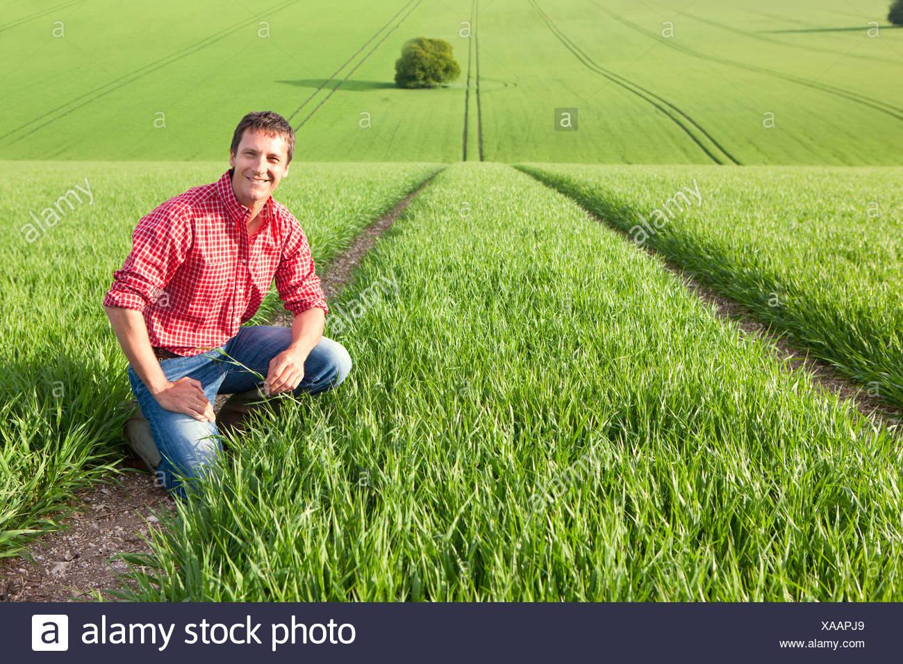 Portrait of smiling farmer in field - Stock Image