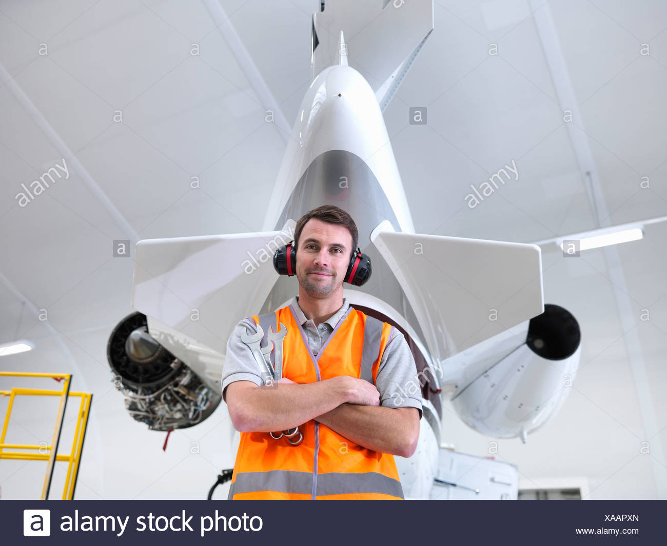 Engineer standing with jet aircraft - Stock Image