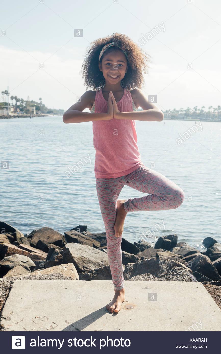 Portrait of schoolgirl practicing yoga tree pose by lakeside - Stock Image