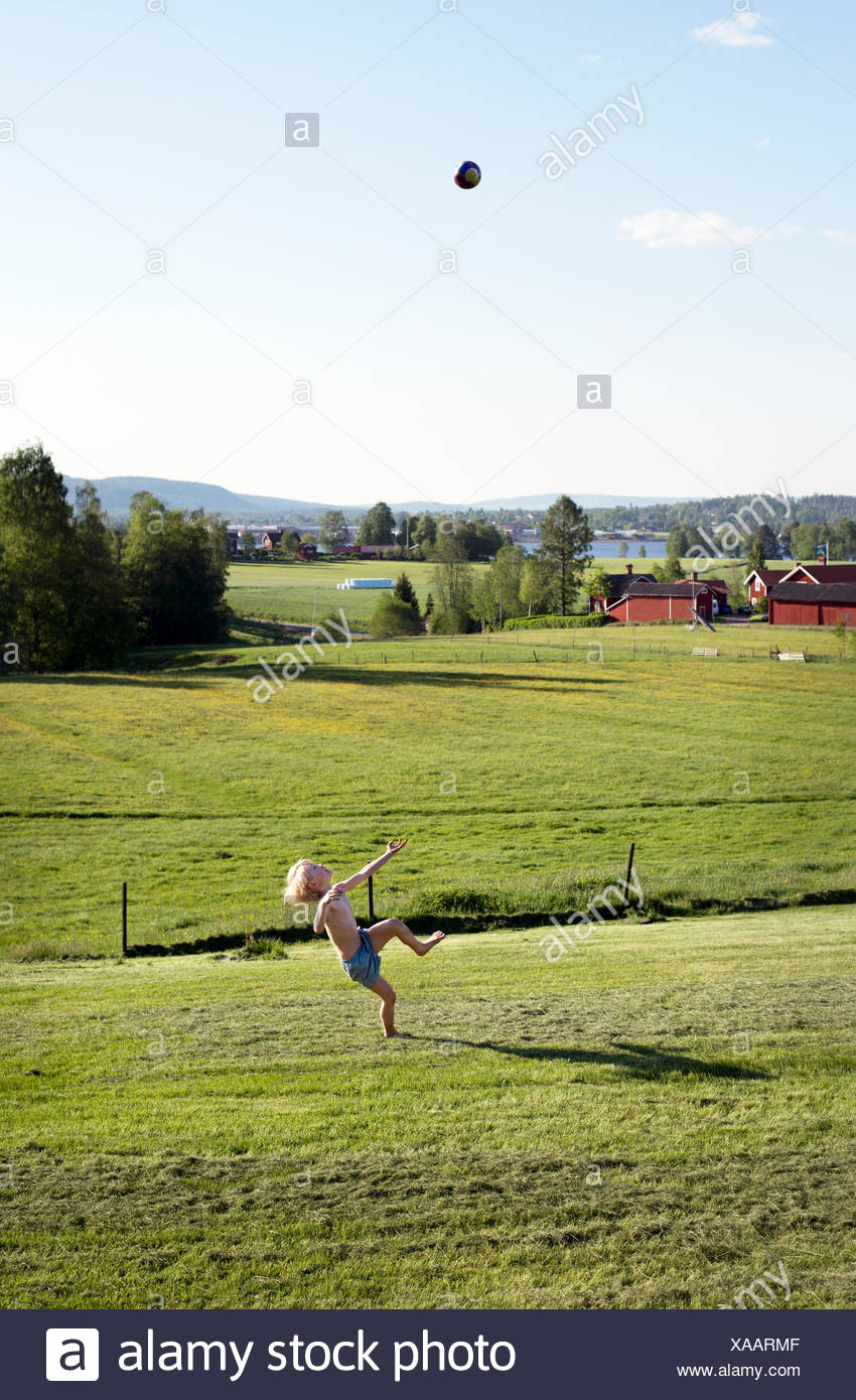 Boy playing ball on grass - Stock Image