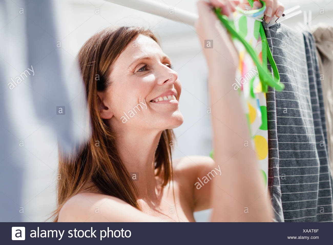 Smiling woman hanging laundry - Stock Image