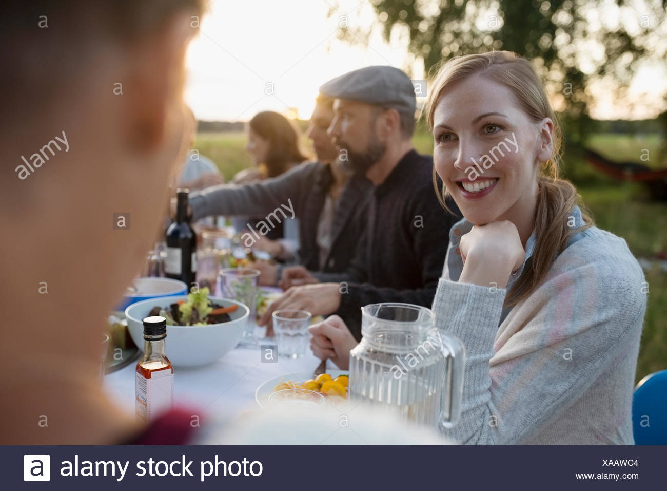 Smiling woman talking to friend, enjoying garden party dinner - Stock Image