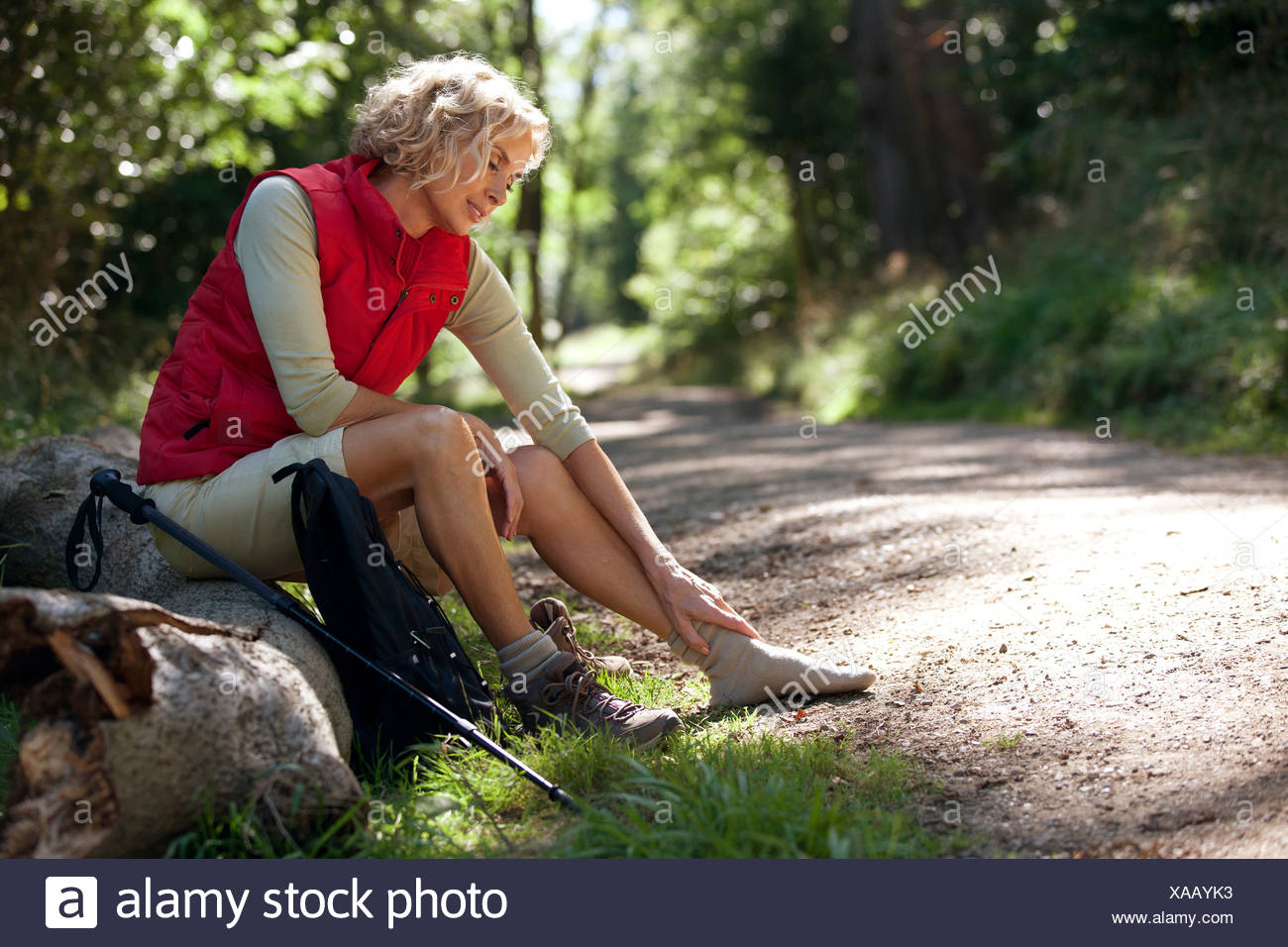 A mature woman resting beside a country path, massaging her sore feet Stock Photo