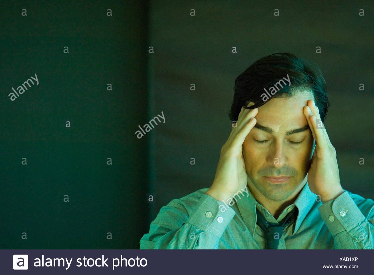 Businessman holding head, eyes closed - Stock Image