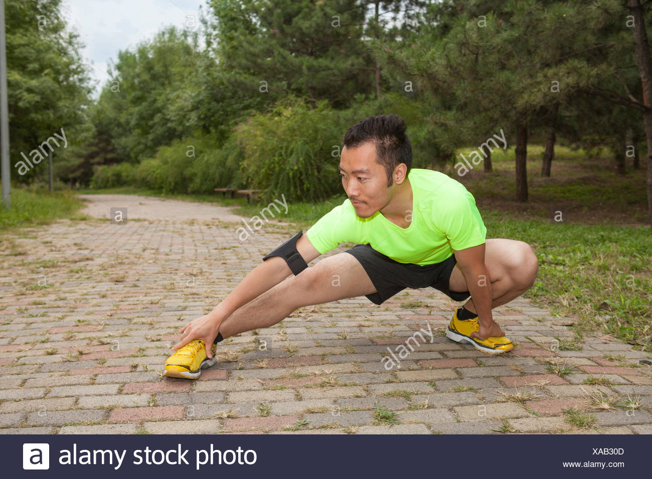 Young male runner crouching and stretching in park - Stock Image