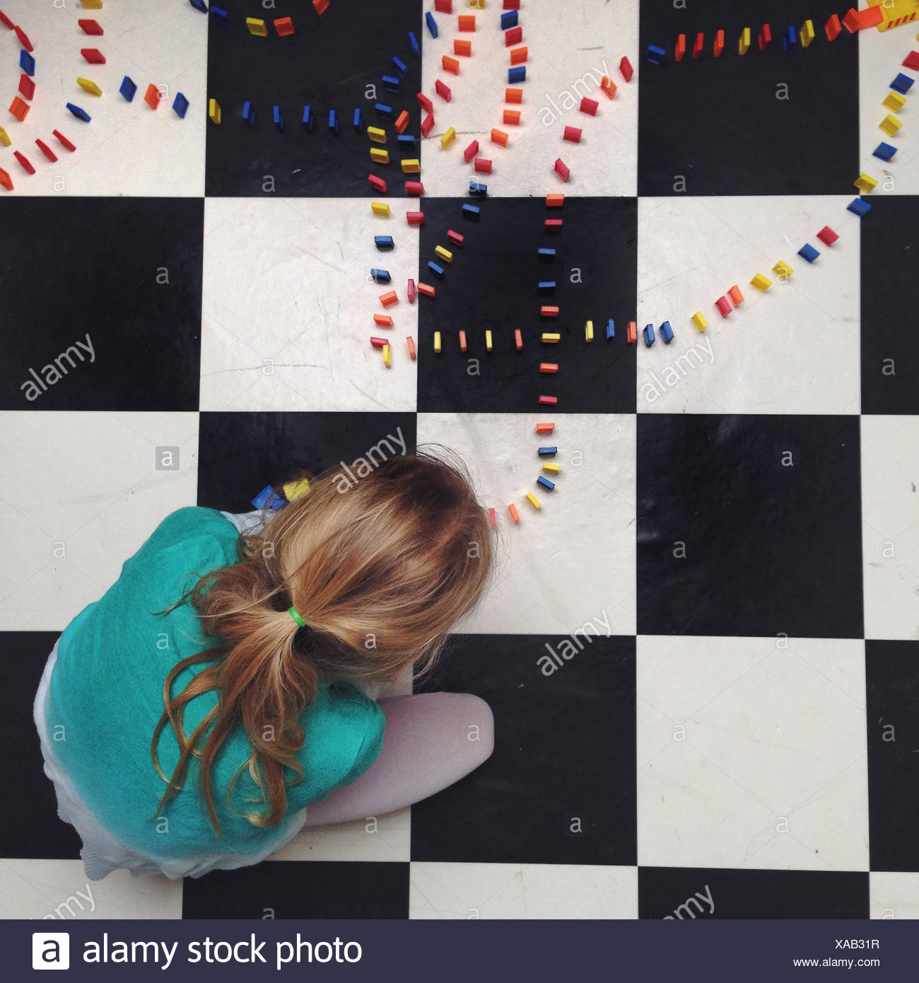 Girl (12-13) girl setting up lines of dominos - Stock Image