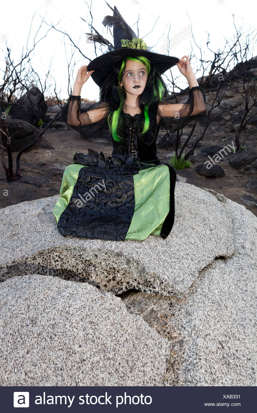 Little young girl costumed as witch sitting on rock looking away - Stock Image