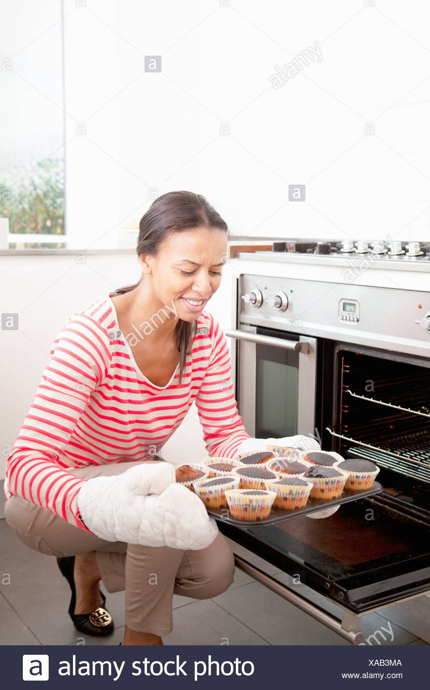 Woman holding tray of burned cupcakes - Stock Image