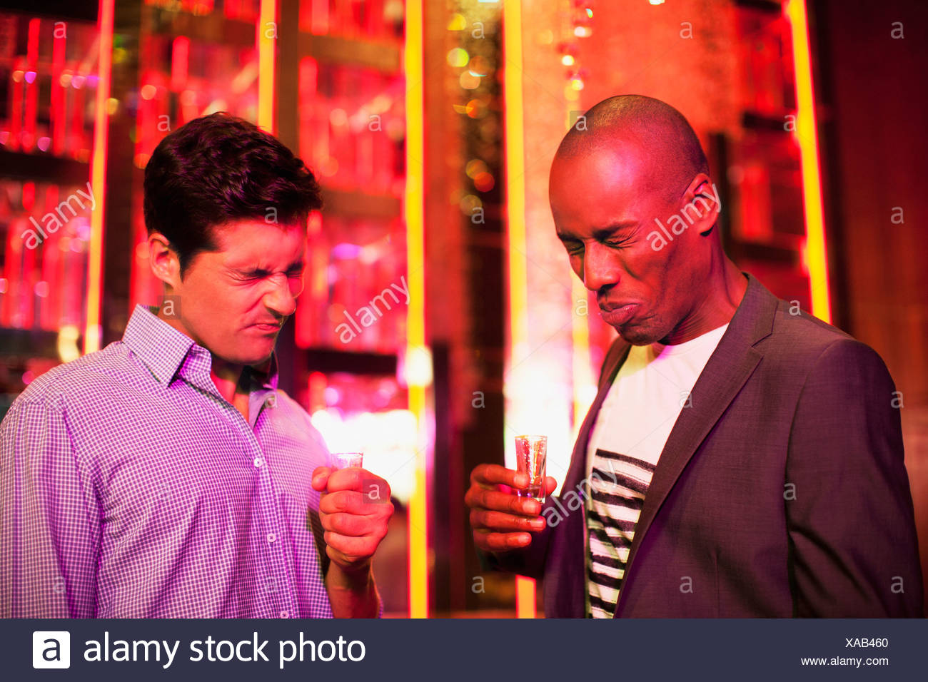 Men with shot glasses making a face in nightclub - Stock Image