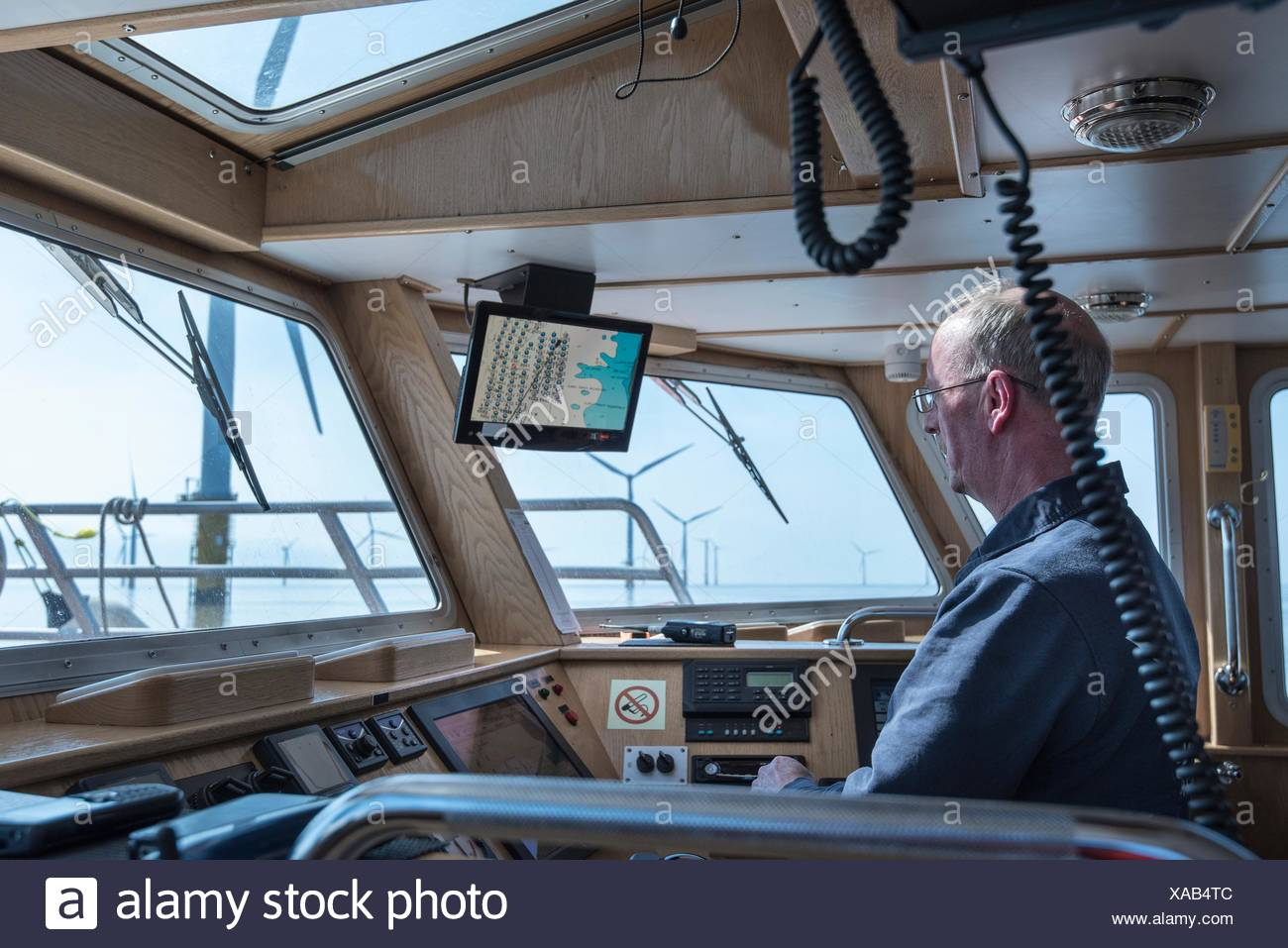 Captain steering service boat at offshore windfarm - Stock Image