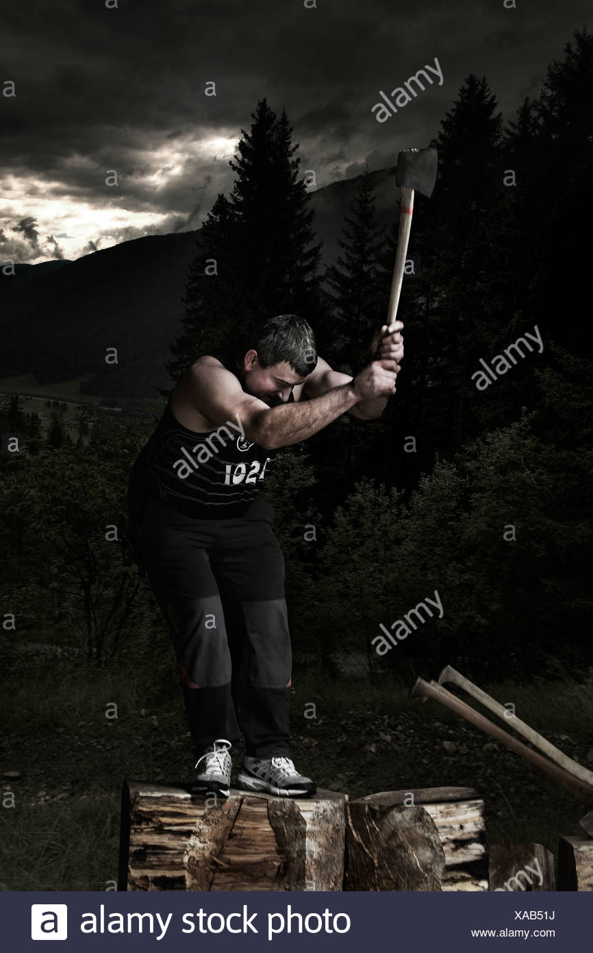 A man chops a tree trunk with an axe during traditional rural sport
