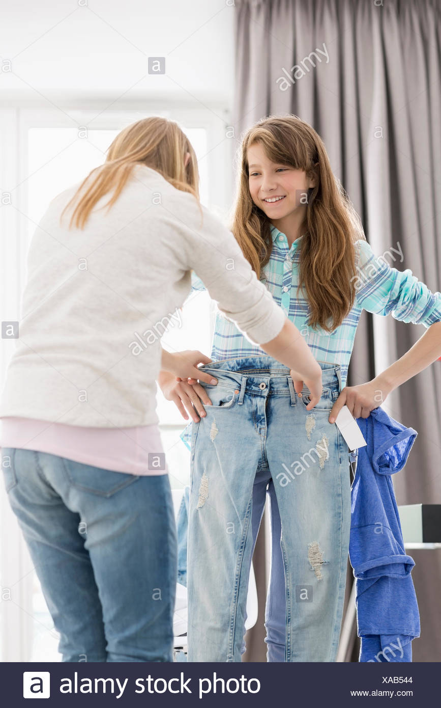Sisters trying on clothes at home - Stock Image