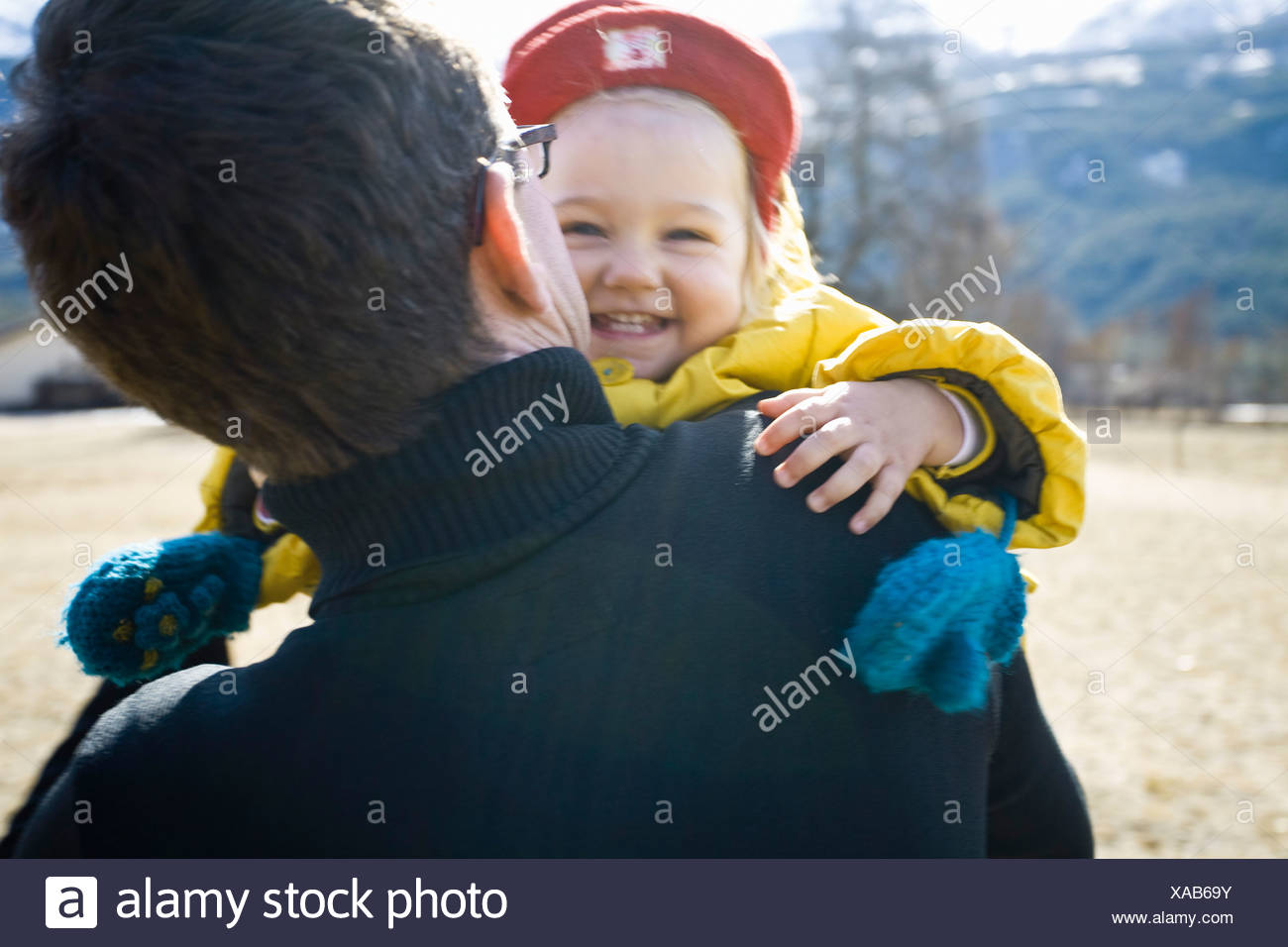 Father carrying baby girl, baby girl smiling - Stock Image