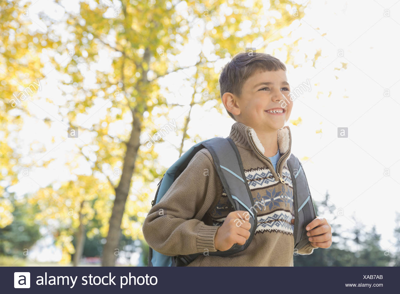 Schoolboy with backpack standing outdoors - Stock Image