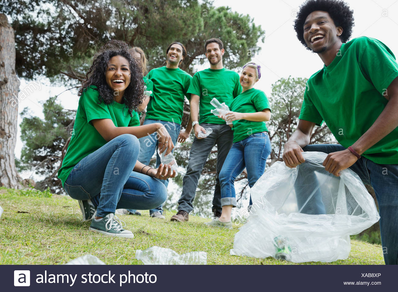 Happy environmentalists collecting empty bottles in plastic bags at park - Stock Image
