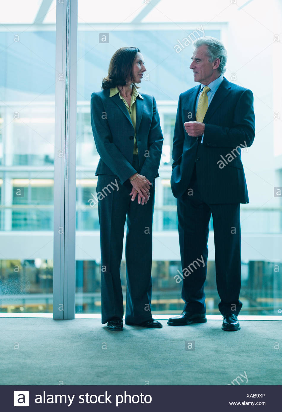 Business people talking near glass wall in office - Stock Image