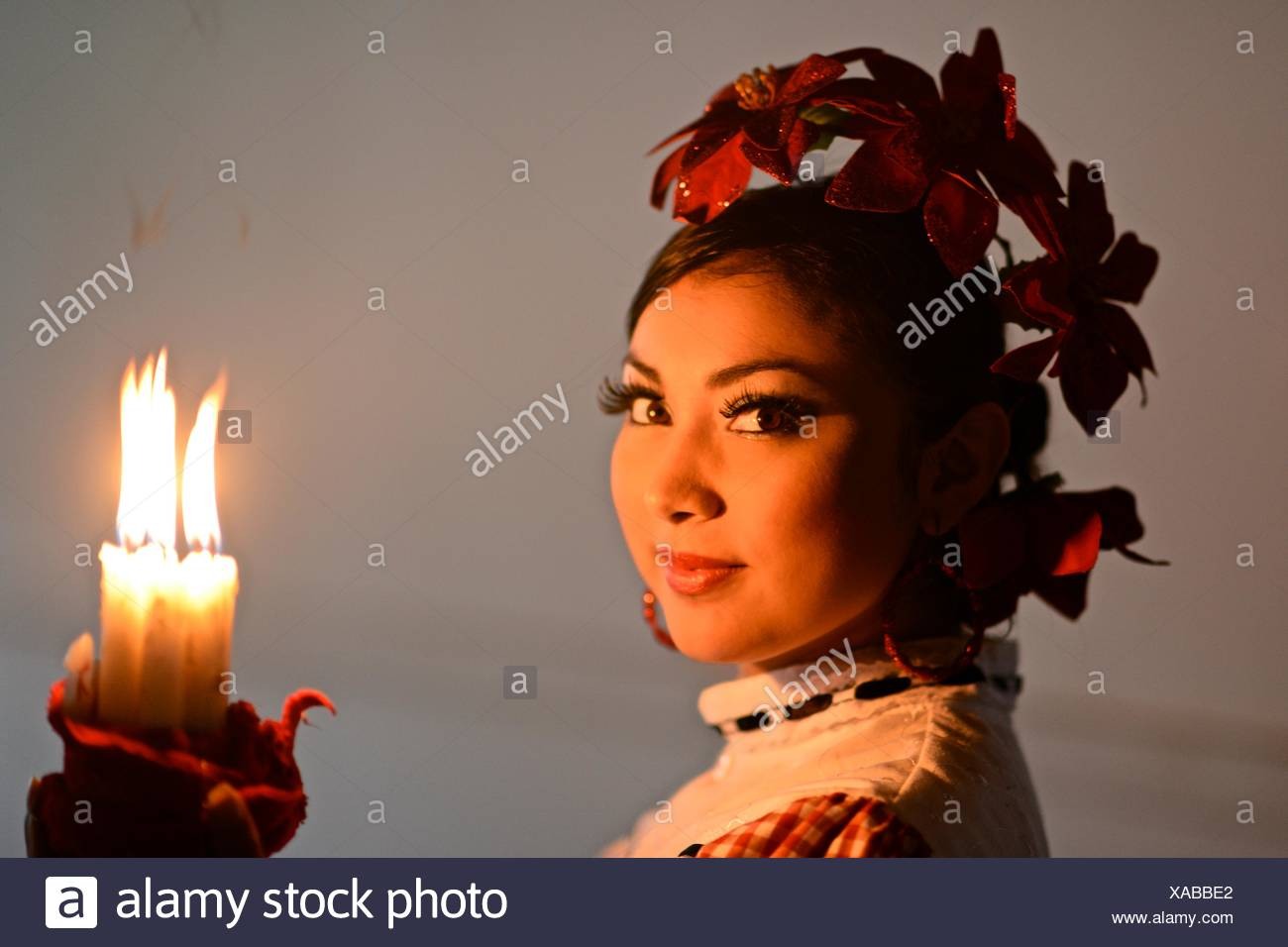 A Cumbia dancer holding candles and looking at camera. - Stock Image