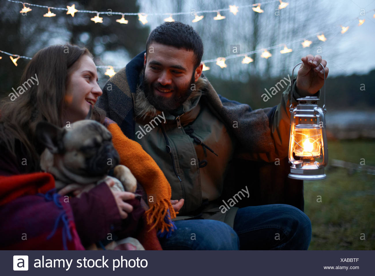 Young camping couple with dog wrapped in blanket - Stock Image