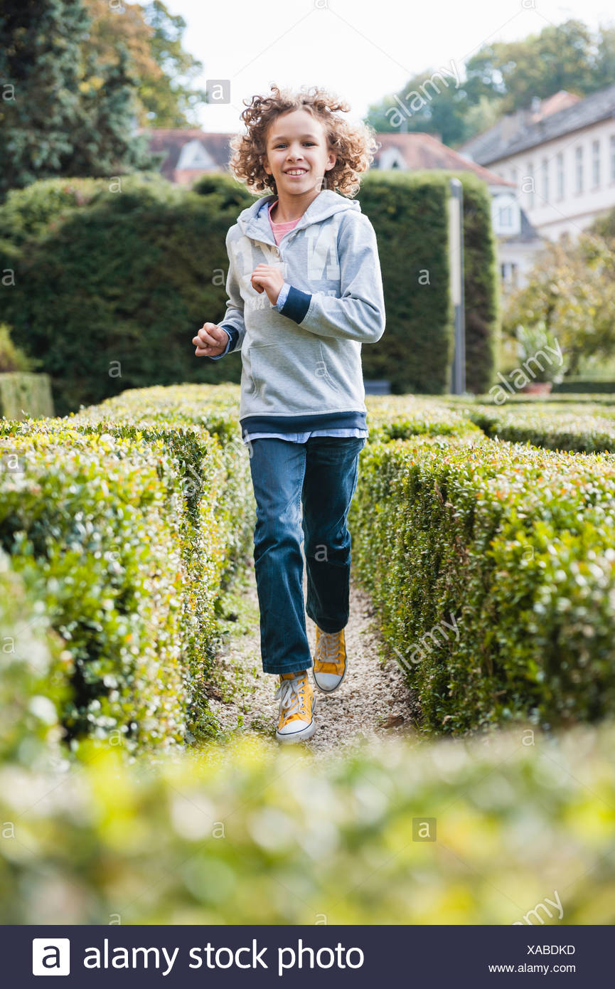 Boy running between hedges - Stock Image