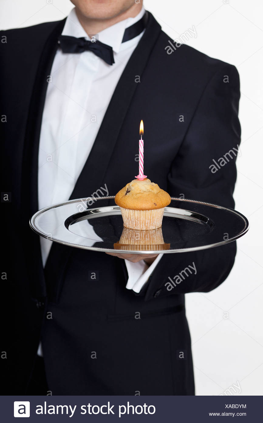 A butler presenting a muffin with a lit birthday candle on a silver tray, focus on hand Stock Photo