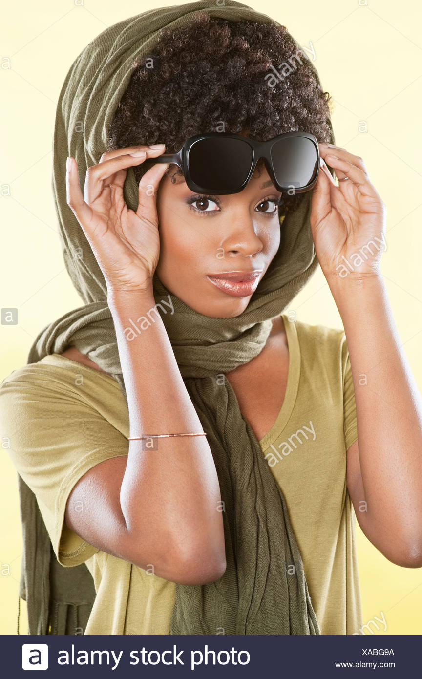 49d338b8dc Portrait of an African American woman holding sunglasses with a stole over  her head