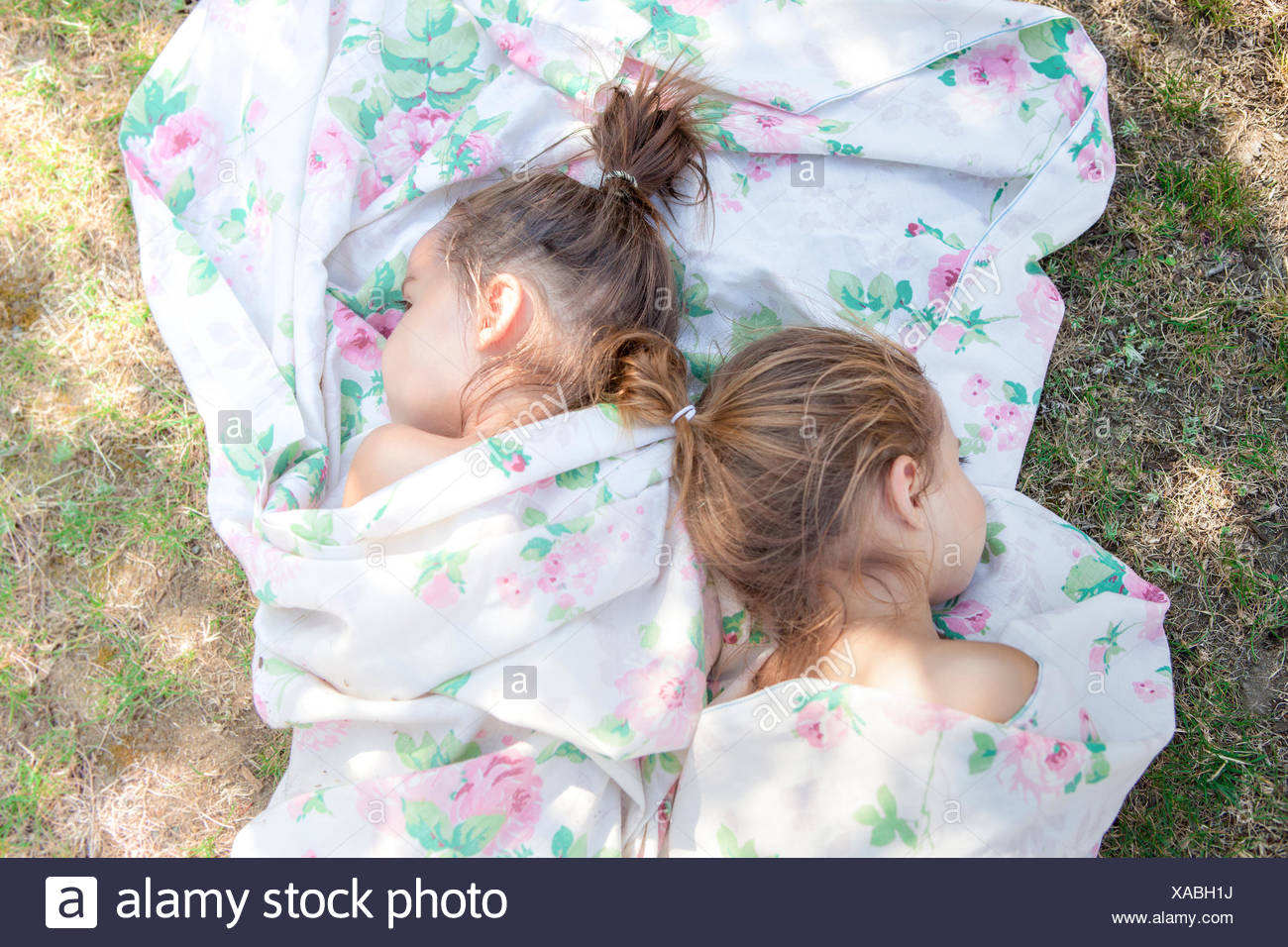 Twin girls napping in floral sheet on grass - Stock Image