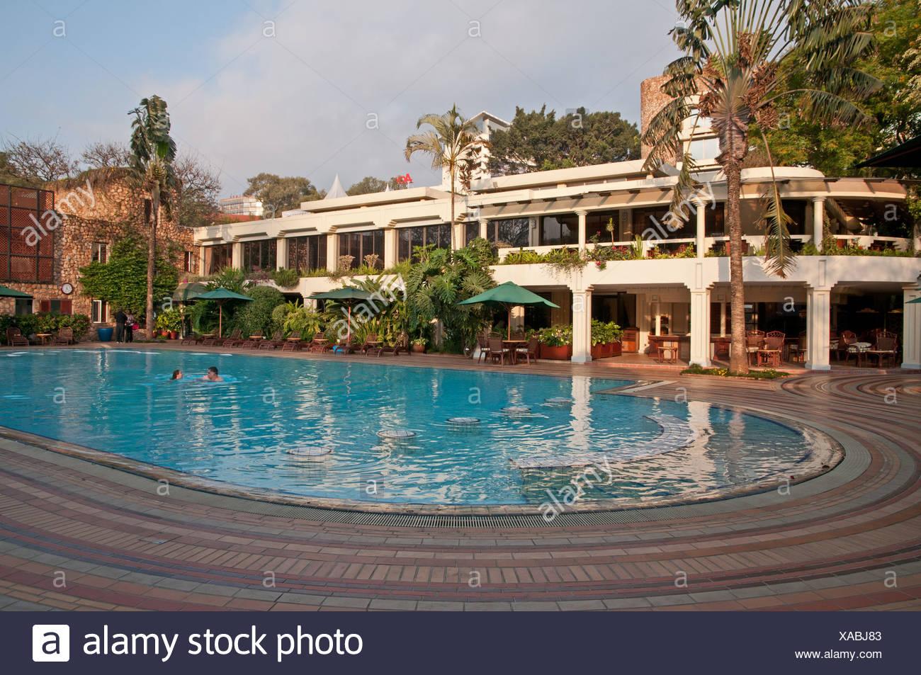 Nairobi Serena Hotel swimming pool with two swimmers Kenya - Stock Image