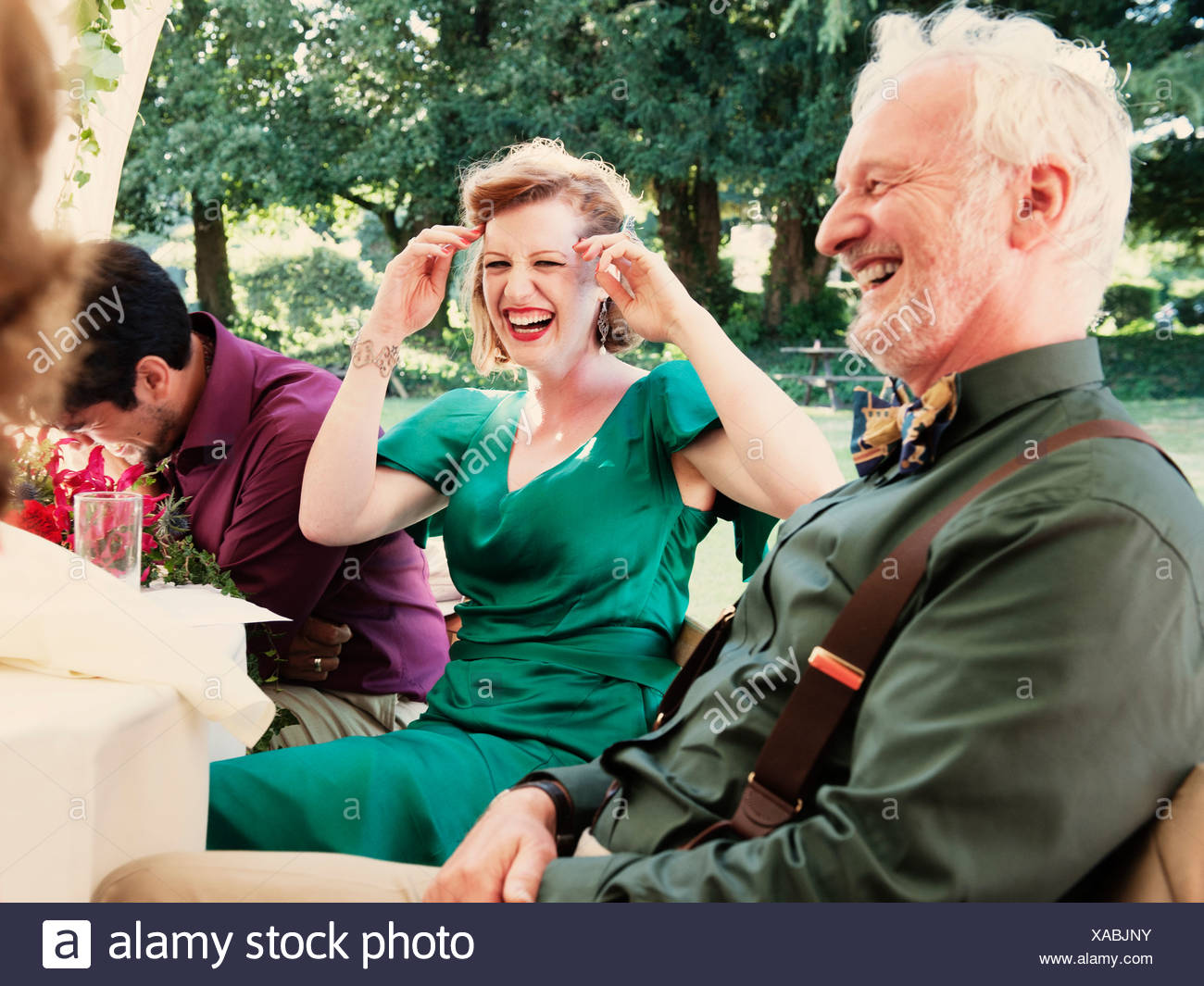 Newly married couple with parents laughing at wedding reception - Stock Image