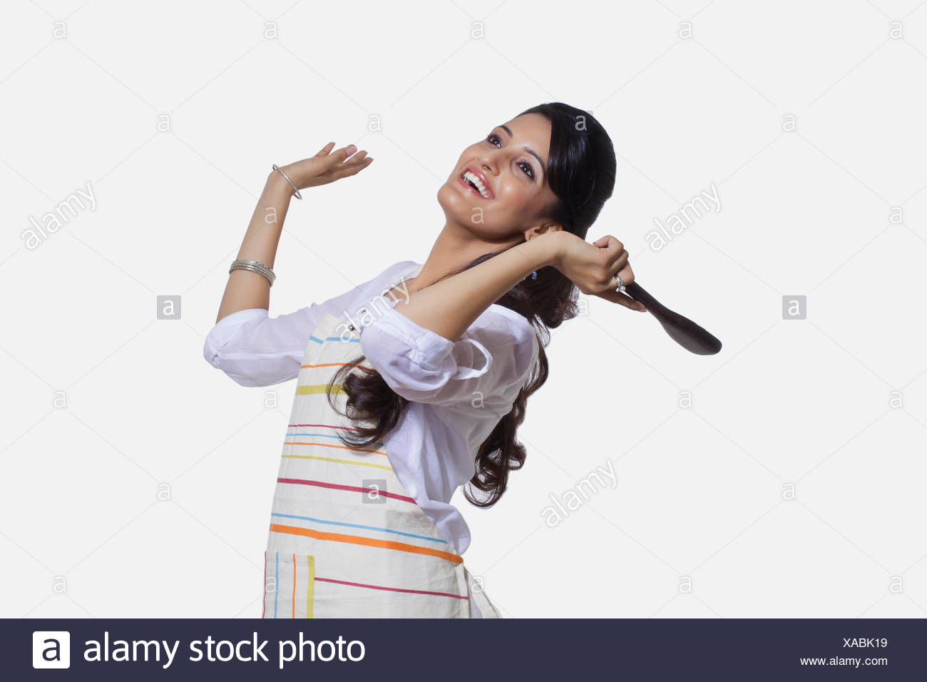 Woman with a cooking utensil rejoicing - Stock Image