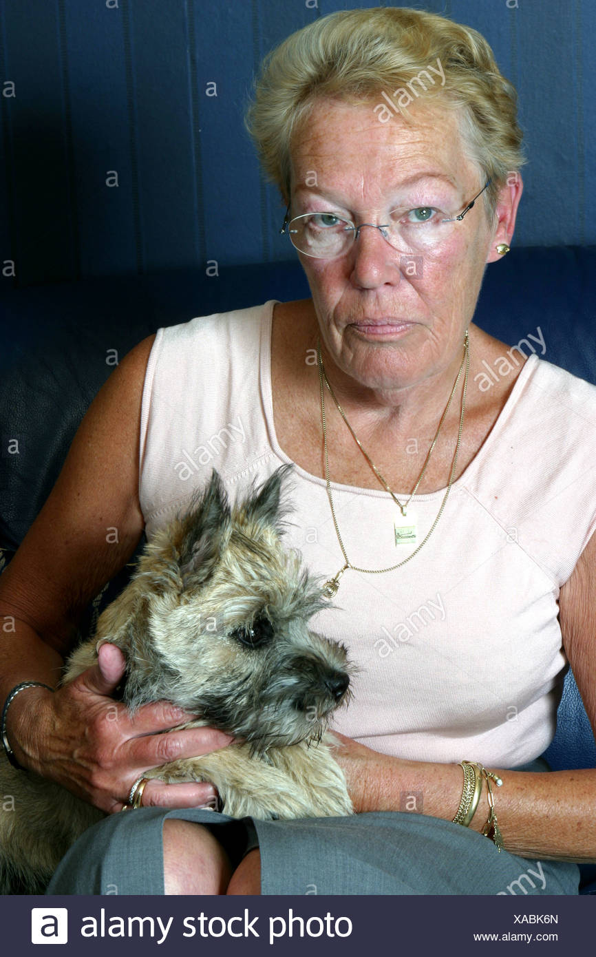 Portrait of a serious face from an elderly woman with dog at home - Stock Image