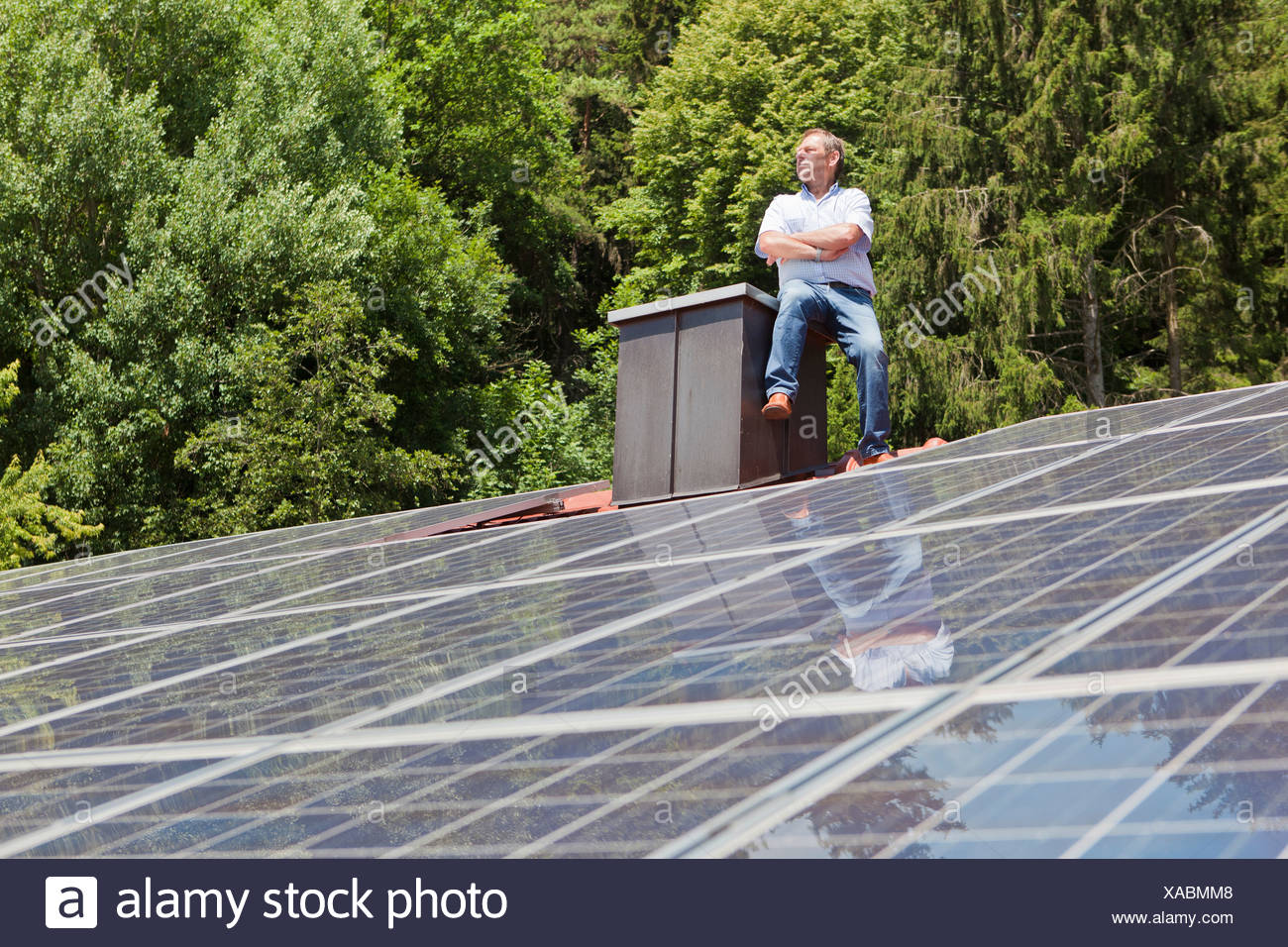 Man standing on solar paneled roof - Stock Image