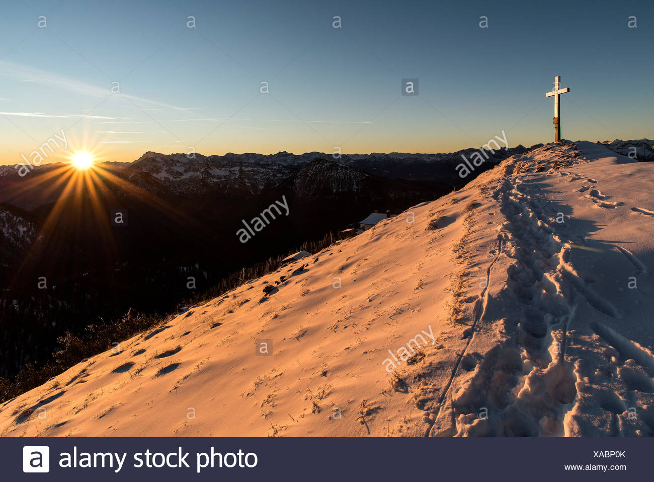 Evening sun at the summit of the Heimgarten, summit cross shines in the snow of the foreground footprints. - Stock Image
