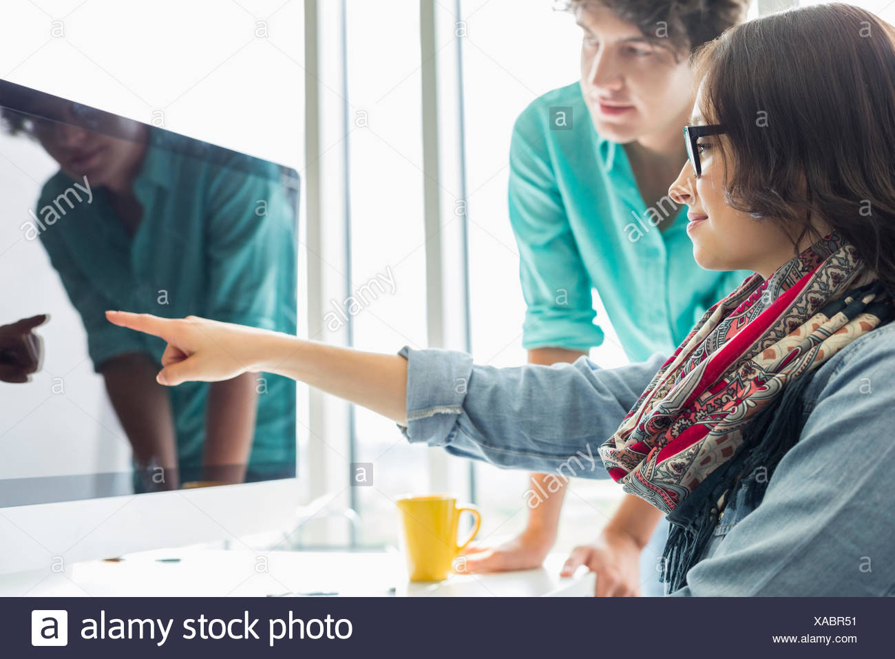 Creative businesswoman showing something to colleague on desktop computer in office - Stock Image