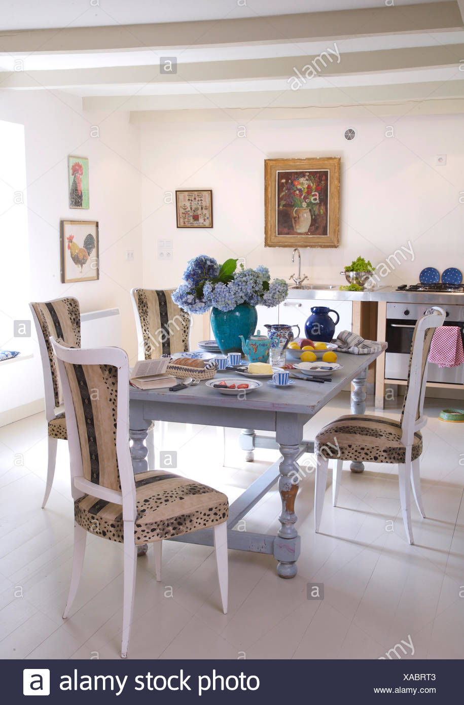 Upholstered white painted chairs at painted blue table in ...