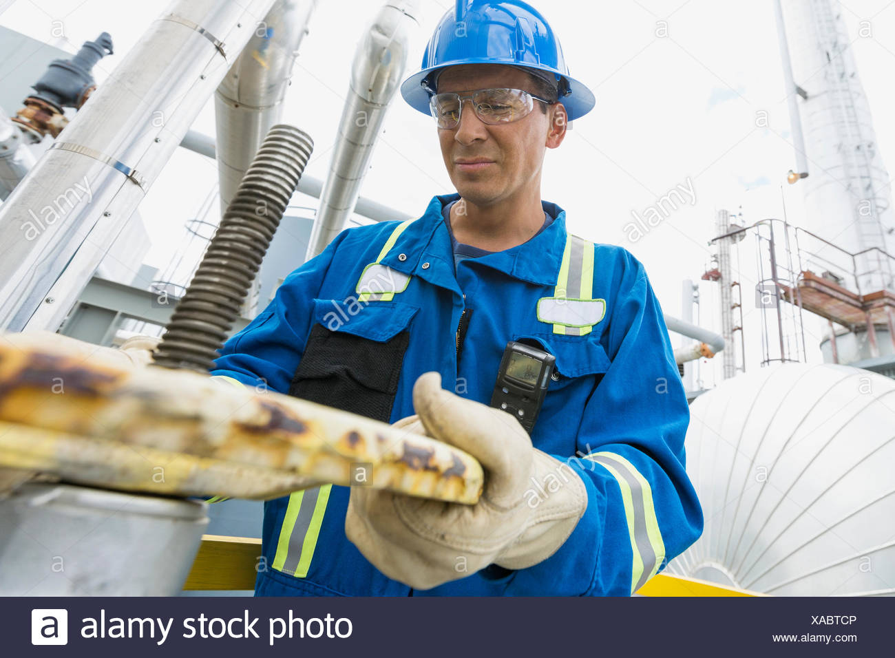 Male worker opening valve at gas plant - Stock Image