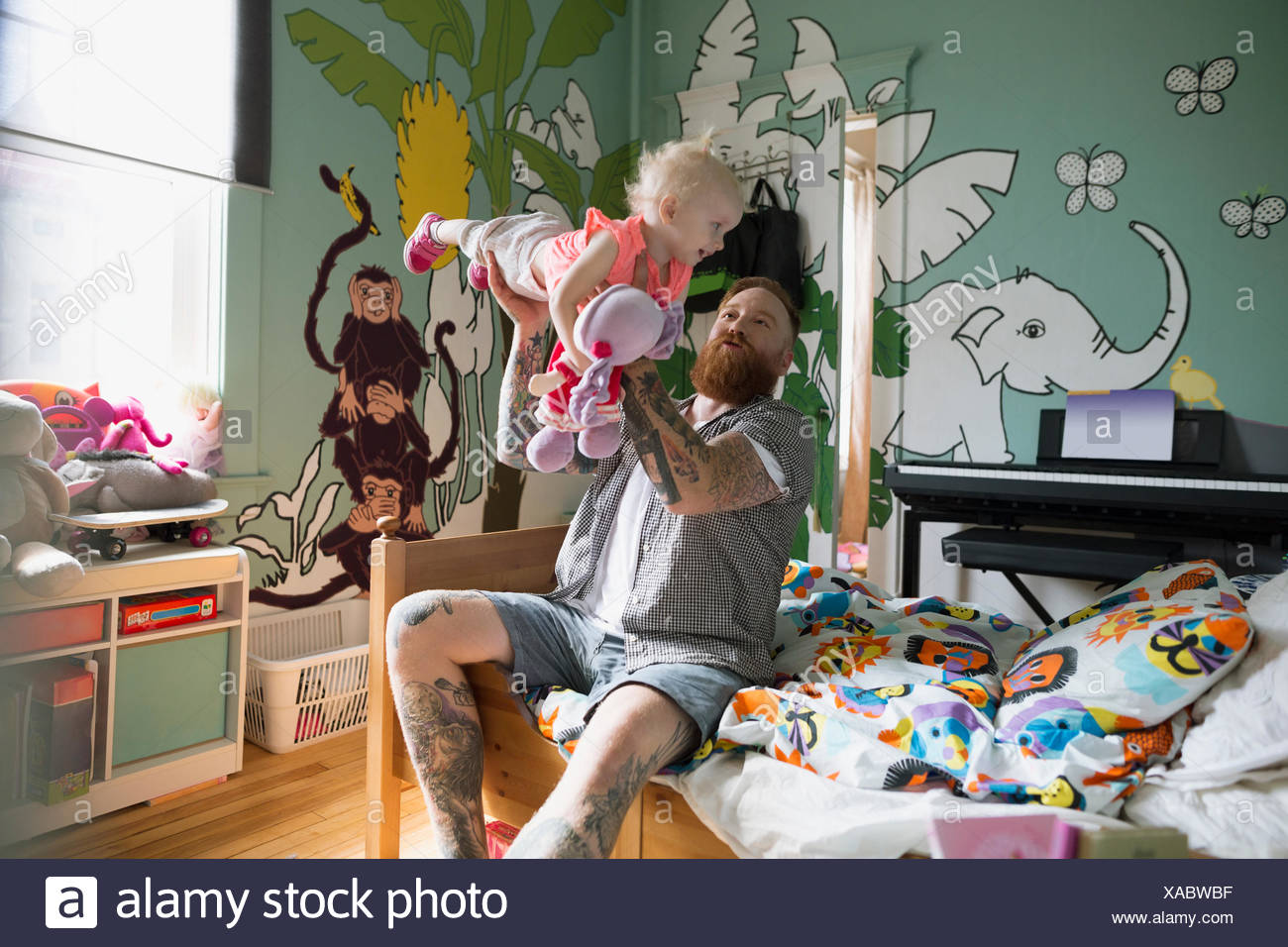 Playful father flying daughter in bedroom - Stock Image