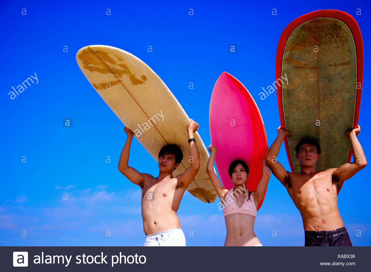 Three people carrying the surfboards on heads and looking away - Stock Image