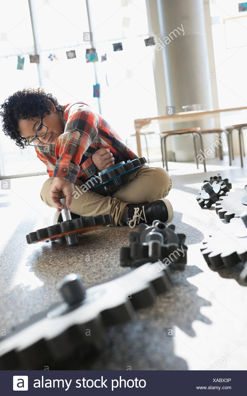 Boy playing with cog pieces in science center - Stock Image