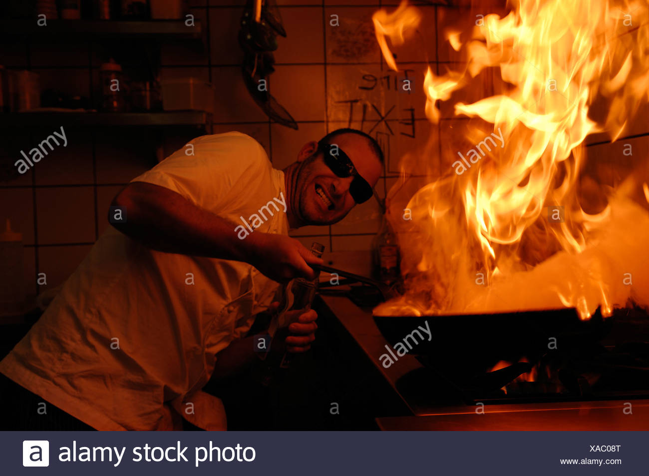 Man with sunglasses holding a burning pan on the stove - Stock Image