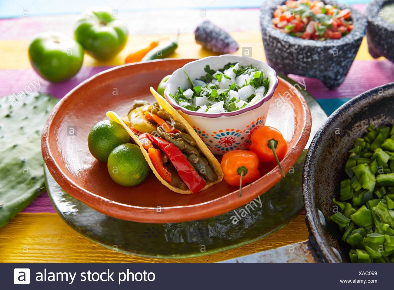 Nopal taco mexican food with chili pepper and ingredients on colorful table. Stock Photo