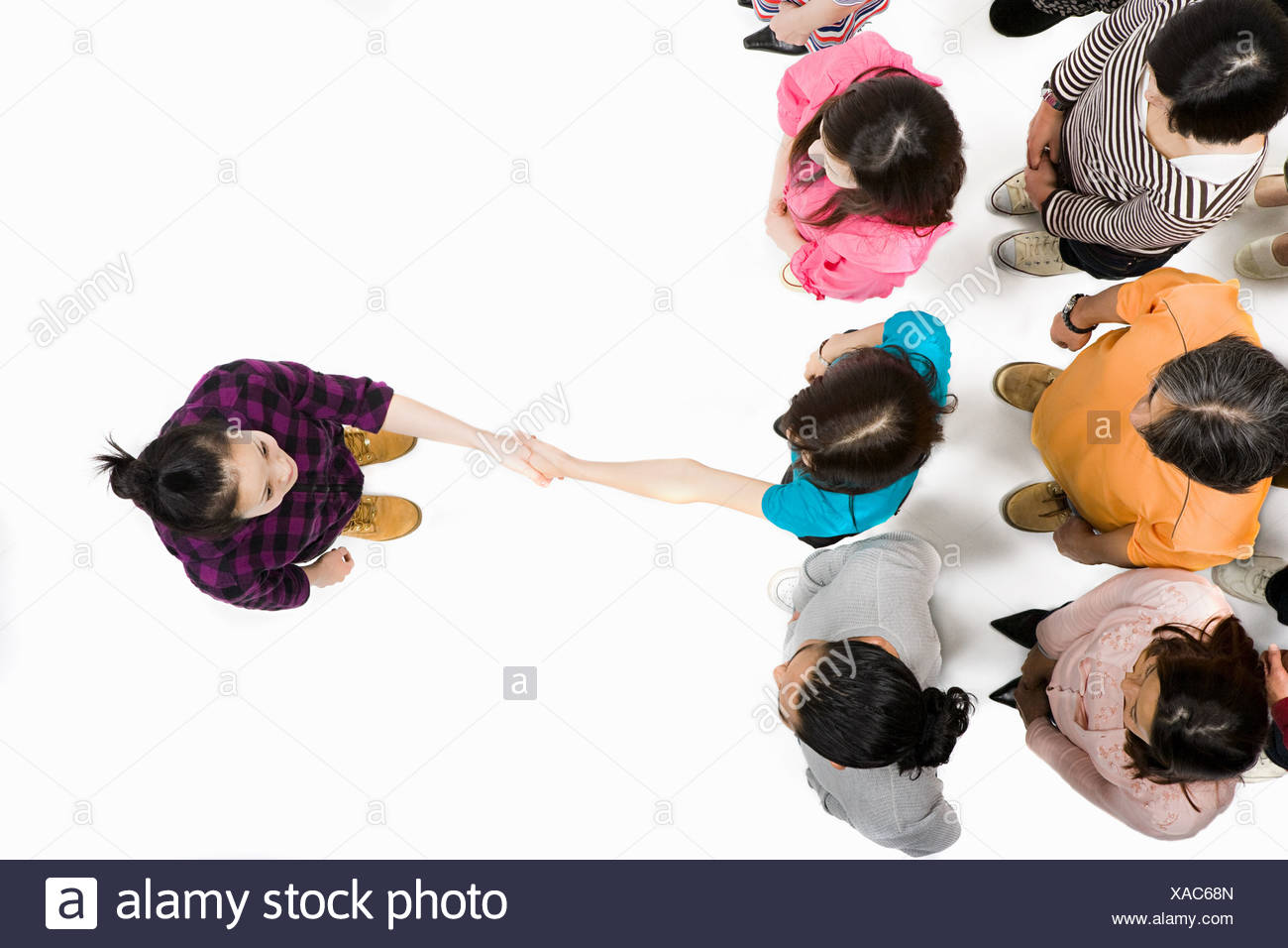 Woman shaking hands with someone in crowd - Stock Image