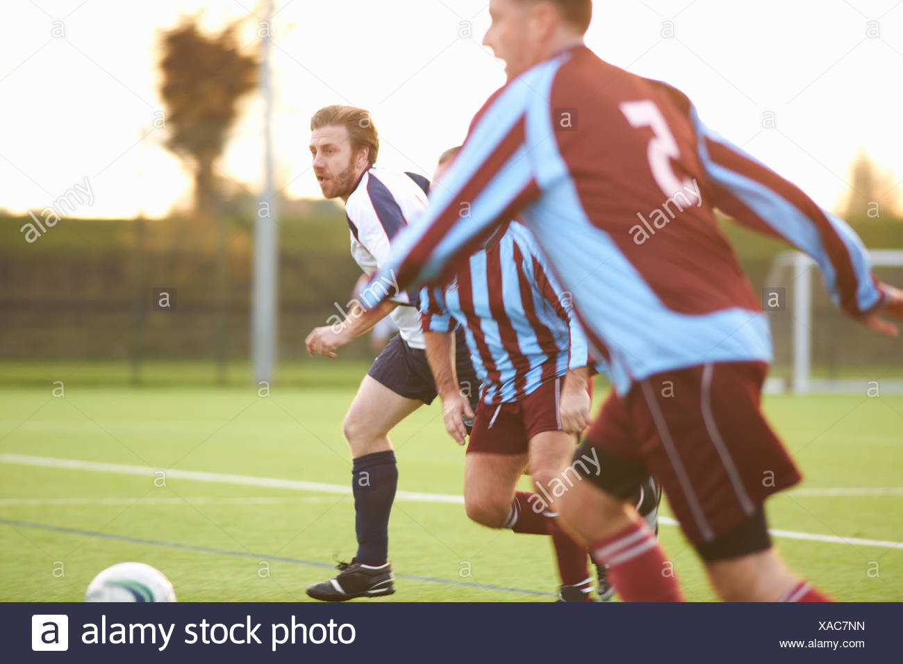 Football players running after ball - Stock Image