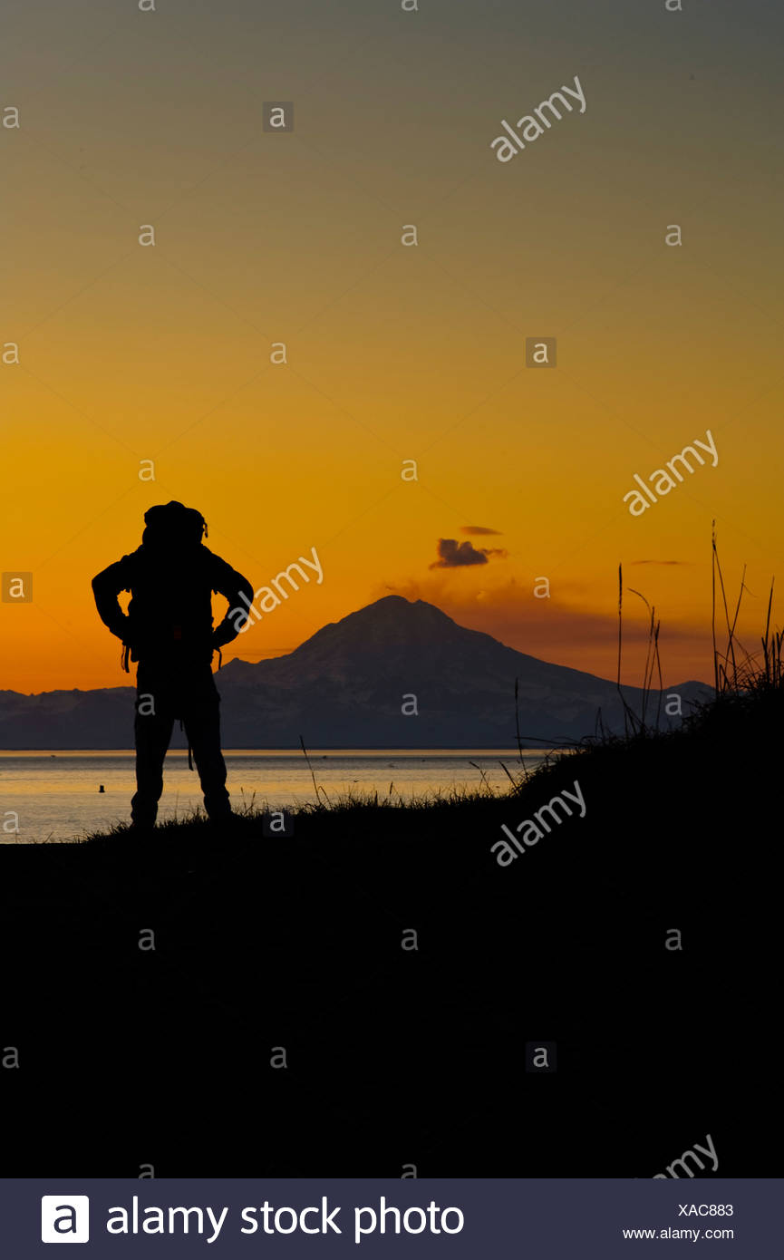 Hiker looking across Cook Inlet at plume rising from Mt. Redoubt, Kenai Peninsula, Southcentral Alaska, Spring - Stock Image